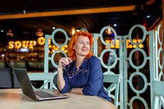 A woman with a smile and a pensive look looks away with glasses in hand behind a stitch in a cafe. A woman, aged, red-haired, in a blue dress and glasses, with a Royalty Free Stock Photo