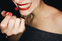 Woman smile with red lips and lipstick at party. Young woman with lipstick party mood portrait Stock Image