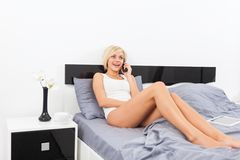 Woman smile talking on cell phone lying on bed Royalty Free Stock Photos