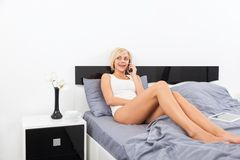 Woman smile talking on cell phone lying on bed Royalty Free Stock Images