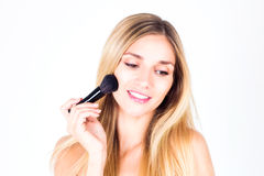 Woman with smile with teeth apply blush on face with large brush Stock Photo