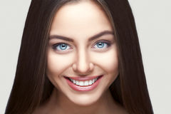 Woman smile. Teeth whitening. Dental care. Portrait of attractive caucasian smiling woman brunette on gray background, studio shot toothy smile face long hair Stock Photos