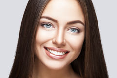 Woman smile. Teeth whitening. Dental care. Portrait of attractive caucasian smiling woman brunette on gray background, studio shot toothy smile face long hair Royalty Free Stock Images