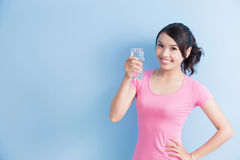 Woman smile to yo. Woman drink water and smile to you  on blue background Royalty Free Stock Images