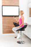 Woman smile watching tv rmote control channel Royalty Free Stock Image