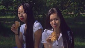 Woman with smile on young face gossip and drinking coffee. Two friends eating breakfast in the park. Happy women eat croissant outdoors. Girls meeting have stock video