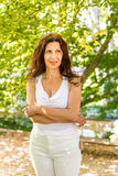 Woman smiles biting her lip. Curvy menopausal woman standing in a park with crossed arms smiles biting her lip Royalty Free Stock Photo
