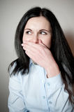 Woman smiles, covers a mouth with a palm Stock Photography