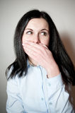 Woman smiles, covers a mouth with a palm Royalty Free Stock Image