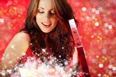 Woman smiles and holding a magic gift in packing Stock Images