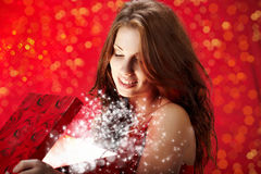 Woman smiles and holding a magic gift in packing Stock Photo