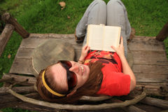 Woman smiles while reading a book on a unique bench. A freckled woman wearing sunglasses smiles up and back at the camera while reading a book on an unique Royalty Free Stock Images