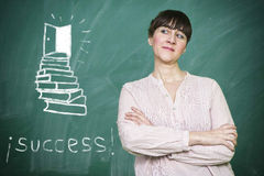 Woman smiles writes on a blackboard the concept of success Stock Image