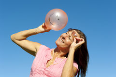 Woman with smiley balloon. An attractive and happy looking mature woman in her fifties, wearing a pink shirt and sunglasses, is holding a colour matching balloon Stock Photos