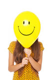 Woman with smiley face balloon. Woman holding balloon with smiley face in front of her face royalty free stock image