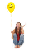 Woman with smiley face balloon. Young woman holding smiley face balloon Stock Photography