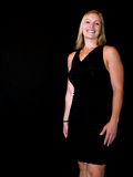 Woman Smiling. Wearing a black dress.  Isolated against a black background Stock Image