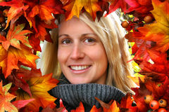 Woman smiling. Woman looking through autumn leaves, smiling stock image