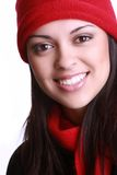 Woman smiling. A portrait of a beautiful young woman smiling and wearing a red woolen cap and scarf stock photo