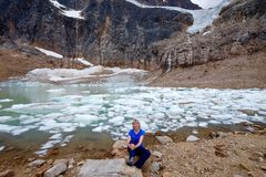 Woman smiling by alpine lake with icebergs under glacier. stock photography
