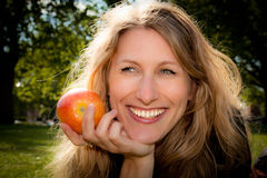 Woman smiling with an apple. An apple a day keeps the doctor away. Beautiful young woman about to eat an apple outdoors Stock Photography