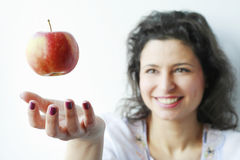 Woman smiling at an apple floating in the air Royalty Free Stock Photo