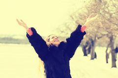 Woman smiling arms raised up to sky, celebrating freedom outdoors Stock Image