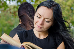Woman smiling as she reads a book Stock Photo