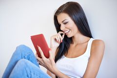 Woman smiling as she reads an sms. Attractive young woman smiling as she reads an sms or text message on her mobile phone while relaxing at home Royalty Free Stock Images