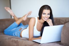 Woman smiling as she relaxes with her laptop Stock Photo