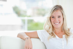 A woman smiling as she sits on the couch Stock Photos