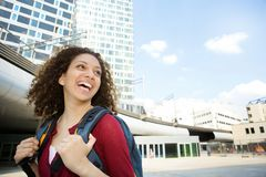 Woman smiling with backpack in the city Royalty Free Stock Images