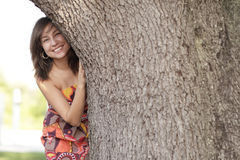Woman smiling behind a tree Stock Photography