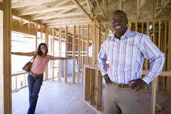 Woman smiling at businessman with hands on hips in paritally built house, portrait Stock Image