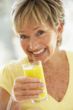 Woman Smiling At Camera Drinking Orange Juice Royalty Free Stock Images
