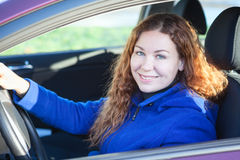 Woman smiling at camera sitting on driver's seat Stock Image