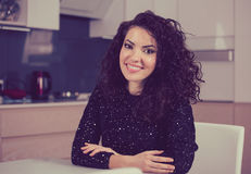 Woman smiling at camera while sitting at home in the kitchen Royalty Free Stock Images