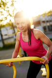 Woman smiling at camera standing on stationary bike. Royalty Free Stock Image
