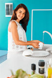Woman smiling at the camera while washing a cup  in blue kitchen Stock Images