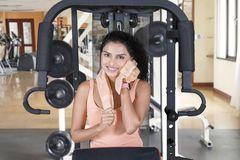 Woman smiling at camera while wiping sweat. Beautiful young woman smiling at the camera while wiping her sweat with a towel after workout on exercise machine at stock images
