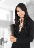 Woman smiling and carrying a book. Asian young businesswoman smiling and carrying a book in the office Stock Images