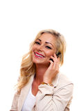 Woman smiling while on cell phone. A woman is smiling while talking on her cell phone royalty free stock photography