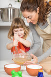 Woman and smiling child whipping to make a cake Royalty Free Stock Images