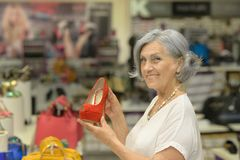 Woman smiling chooses shoes Stock Image