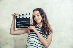 Woman smiling with clapper board movie audition concept. Young pretty woman actress smiling portrait posing for audition analog photography vintage color effect stock photography