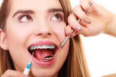 Woman smiling cleaning teeth with braces Stock Images