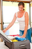 Woman smiling and closes the suitcase Stock Image