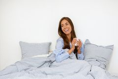 Woman smiling with cup of tea in bed Royalty Free Stock Image