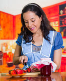 Woman smiling and cutting some strawberries for her recipe, a pot of jam on the side Royalty Free Stock Photos