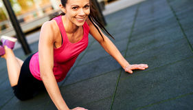 Woman smiling doing a modified push up. Royalty Free Stock Photo